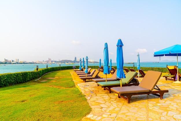 Stuhl pool oder bett pool und sonnenschirm rund um pool mit meer, urlaub und urlaubskonzept