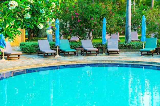 Stuhl pool und sonnenschirm rund um pool mit kokospalme