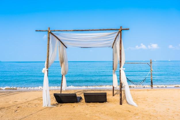 Stuhl sonnenschirm und lounge am schönen strand meer ozean am himmel
