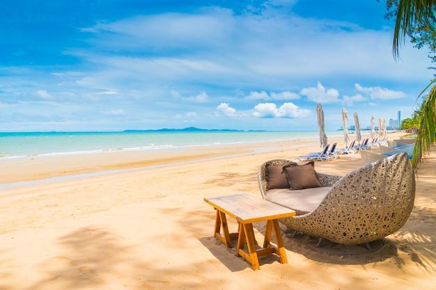 Stuhl und tabelle, die auf dem strand und dem meer mit blauem himmel speisen