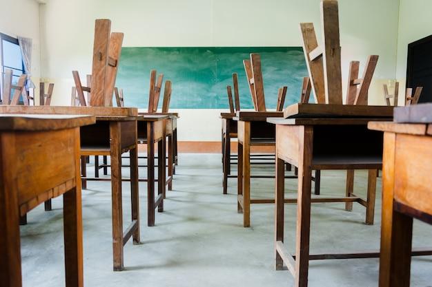 Stuhl und tabelle im klassenzimmer mit schwarzem bretthintergrund