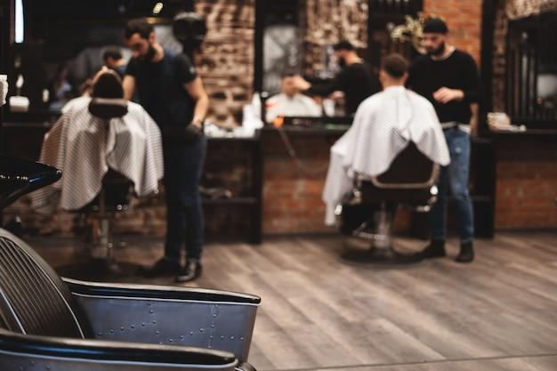 Stuhl zum waschen der haare im friseursalon. friseursalon interieur. brutaler ort. ledersessel mit metallpolsterung