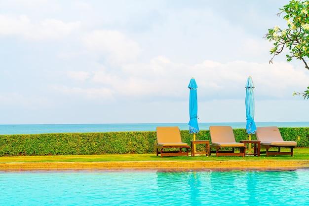 Stuhlpool und sonnenschirm rund um den pool mit ozean-meer-hintergrund