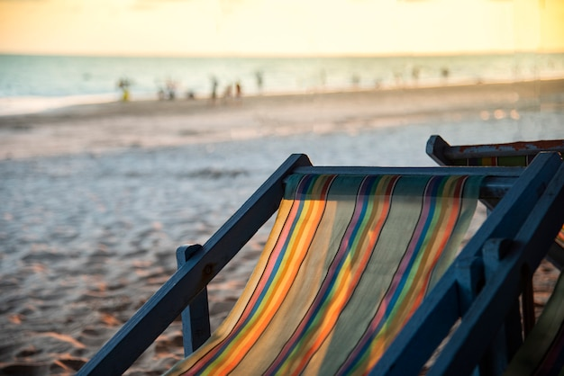 Stuhlstrand mit sonnenuntergang auf seeferien des sandigen strandes des sommers