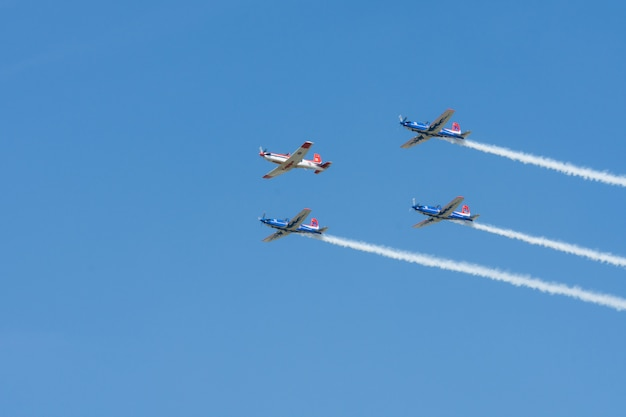 Stuntflugzeuge fliegen in formation gegen strahlend blauen himmel bei flugshowleistung