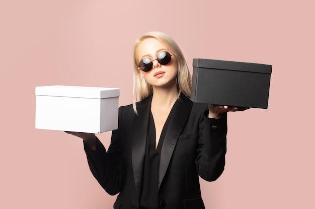 Style blondine in blazer und sonnenbrille mit geschenkboxen auf pink