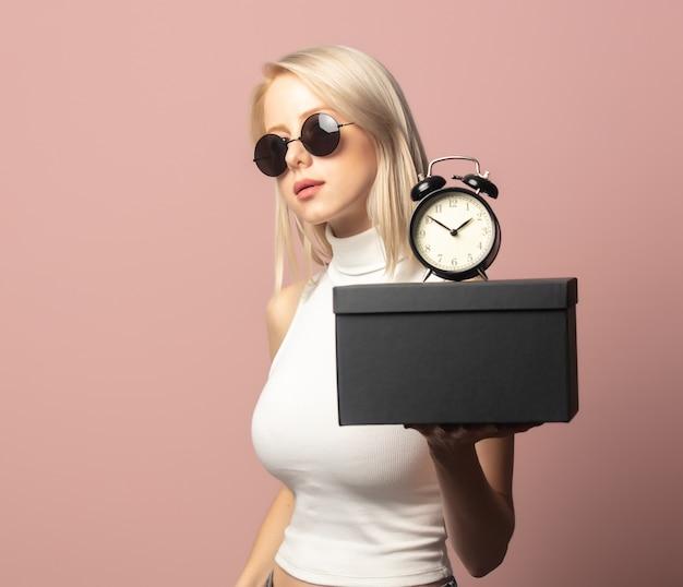 Style blondine in top und sonnenbrille mit wecker und schwarzer geschenkbox auf pink