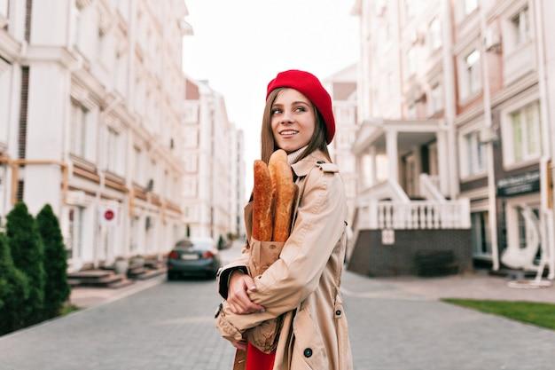 Stylich moderne hübsche frau, die rote baskenmütze und beige graben trägt
