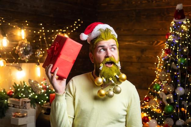 Styling santa hipster mit geschenk, das auf dem hölzernen hintergrund des weihnachtsfestes aufwirft. frohe feiertagsfeier