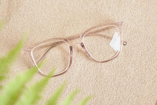 Stylische brille in einem transparenten kunststoffrahmen auf dem sand
