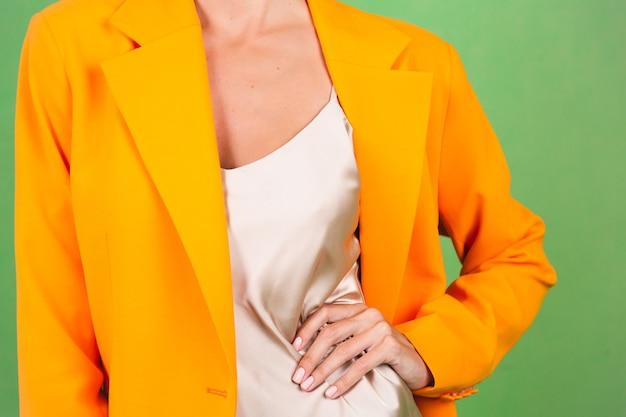 Stylische frau in seidenbeigem kleid und orangefarbenem oversized-blazer auf grün, kein kopfschuss