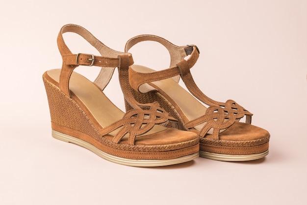 Stylische rosa sandalen für damen aus wildleder auf rosa hintergrund. sommerschuhe für frauen.