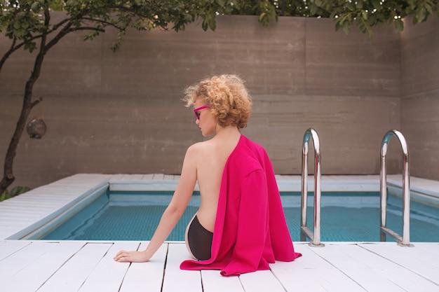 Stylische rothaarige lockige junge frau, die am schwimmbad sitzt
