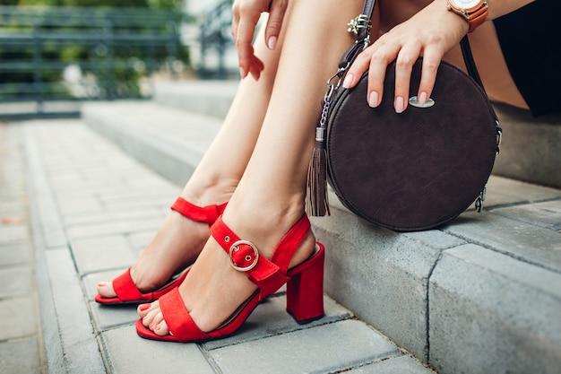Stylische schuhe und accessoires. junge frau, die moderne rote sandaletten trägt und handtasche hält