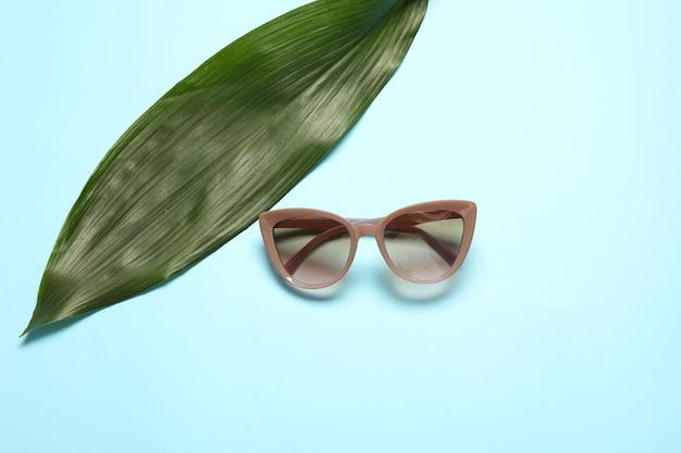 Stylische sonnenbrille und tropisches blatt
