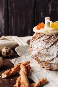 Stylischer osterkuchen mit marshmallows und gummibärchen auf pergamentpapier mit eiern und grissini
