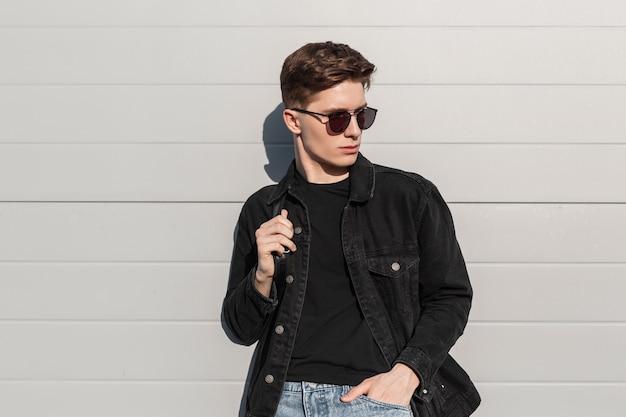 Stylischer städtischer junger mann des porträts mit frisur in modischer schwarzer jeans trägt in trendiger sonnenbrille