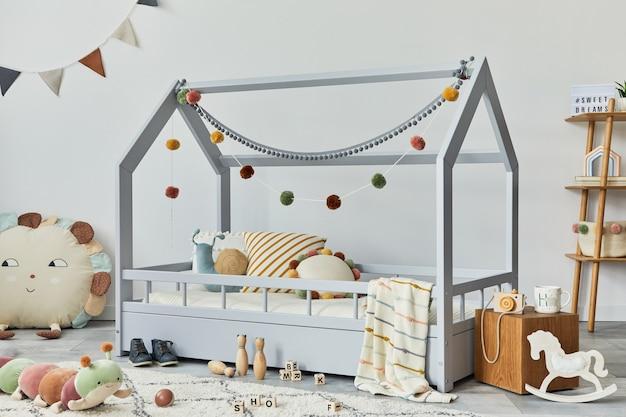 Stylisches skandinavisches kinderzimmer mit kreativem bettspielzeug und hängender textildekorationsvorlage