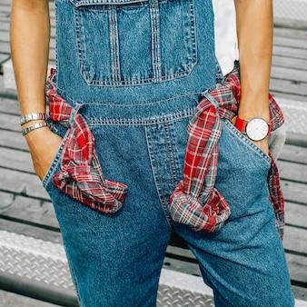 Stylisches urban girl in hemd und jeansoverall in der stadt