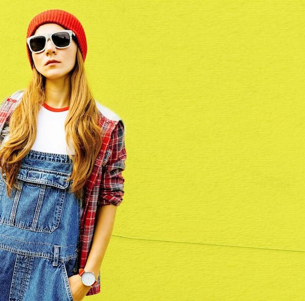 Stylisches urbanes mädchen in kariertem hemd und jeansoverall steht an der gelben wand