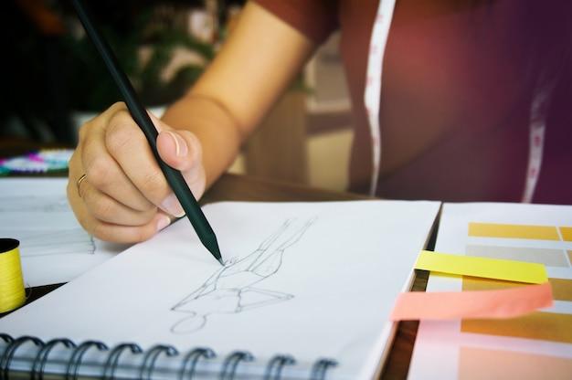 Stylish fashion designer arbeiten als skizze der neuen kollektion im atelier. kreatives designkonzept