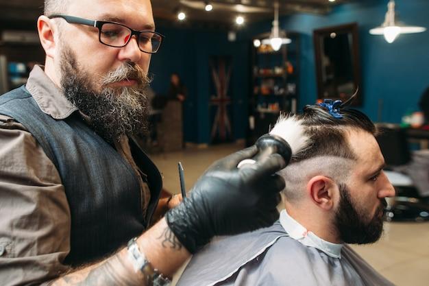 Stylist, der kundenkopf-seitenansicht rasiert