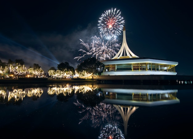 Suan luang royal garden rama ix mit feuerwerk und reflex auf dem wasser in der nacht.