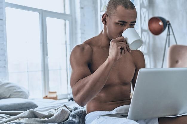 Suche nach aktuellen nachrichten im internet. hübscher junger afrikaner, der kaffee trinkt und computer benutzt