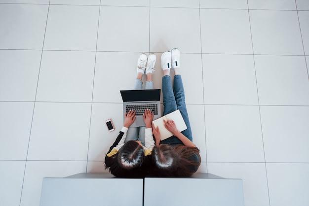 Suche nach den spezifischen informationen. draufsicht der jungen leute in der freizeitkleidung, die im modernen büro arbeiten