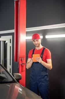 Suche nach informationen. junger beschäftigter männlicher autoreparaturmann, der tablette beim stehen in der nähe des autos in der autowerkstatt betrachtet