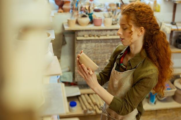 Suche nach inspiration. zufriedene langhaarige töpfermeisterin beobachtet ihre ersten kreationen, während sie sich in der nähe der töpfersammlung aufhält