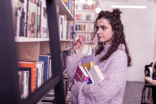 Suche nach interessanter literatur. skeptische junge dame, die ein paar bücher trägt, während sie sich mit ihnen in der bibliothek bewegt