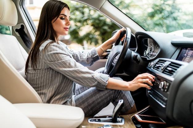 Suche nach lieblingsmusik. junge attraktive frau, die knöpfe lächelt und drückt, während sie ein auto fährt