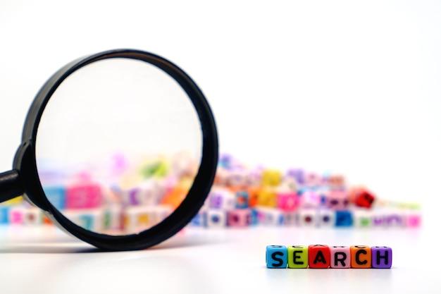 Suche wort mit der lupe auf alphabet buchstaben perlen
