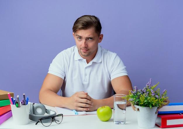Suchen junger hübscher männlicher student, der am schreibtisch sitzt
