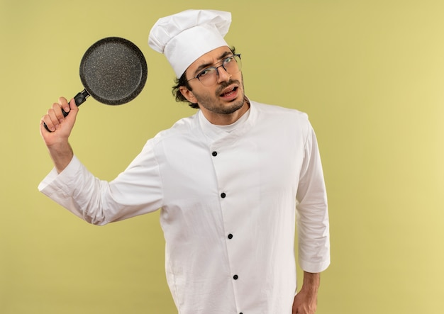 Suchen unzufriedener junger männlicher koch mit kochuniform und brille, die bratpfanne auf grünem hintergrund anhebt