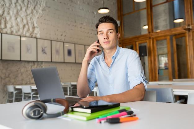 Suchender junger hübscher mann, der im mitarbeitenden büro sitzt