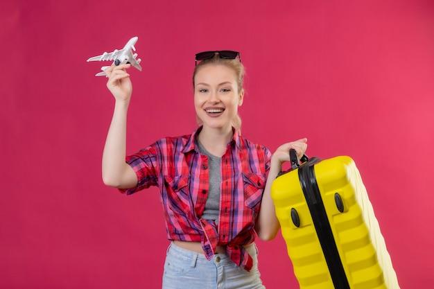 Suchender junger weiblicher reisender, der rotes hemd in den gläsern hält, die koffer und spielzeugplan auf isolierter rosa wand halten