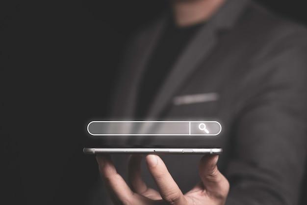 Suchmaschinenoptimierung oder seo-konzept, geschäftsmann hält smartphone für die verwendung von eingabeschlüsselwörtern und das suchen und finden von informationen.
