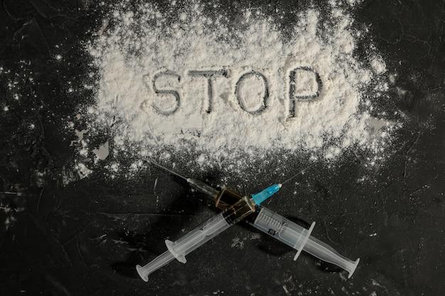 Suchtmittel. heroin in einer spritze und die aufschrift stop kokain auf einem schwarzen tisch. das konzept der drogensucht. sicht von oben