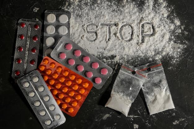 Suchtmittel. lsd und das wort kokain auf dem schwarzen tisch. das konzept der drogensucht. sicht von oben
