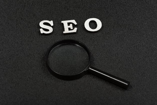 Suchwort oder seo-konzept und lupe auf schwarzem hintergrund. nahansicht