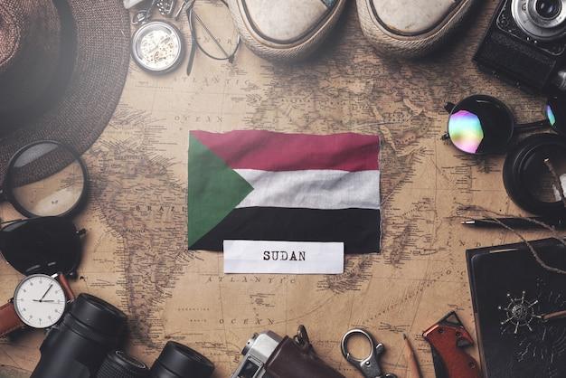 Sudan-flagge zwischen dem zubehör des reisenden auf alter weinlese-karte. obenliegender schuss