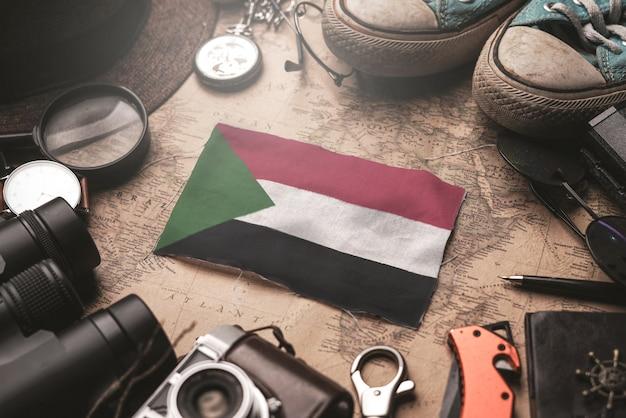 Sudan-flagge zwischen dem zubehör des reisenden auf alter weinlese-karte. touristisches bestimmungsort-konzept.