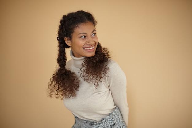 Sudio-foto der attraktiven jungen dunkel gesündigten frau mit dem gelockten langen haar, das geflochten wird, glücklich beiseite schaut und hände hinter ihrem rücken hält, lokalisiert über beigem hintergrund