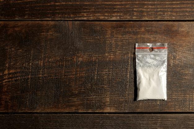 Süchtig machende kokaindrogen in einem paket auf einem braunen holztisch. konzept der drogensucht