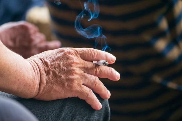 Süchtig machender raucher mit hand halten zigarettentabak zigarre lebensstil mit rauch unter nichtraucherkampagne
