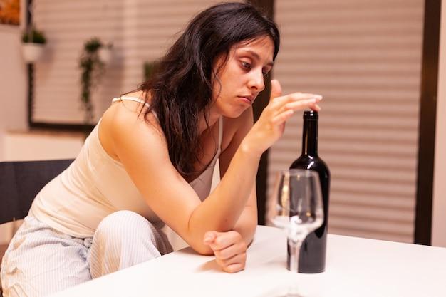 Süchtige frau, die allein zu hause trinkt. unglückliche person, die an migräne, depression, krankheit und angst leidet und sich mit schwindelsymptomen erschöpft fühlt und alkoholismusprobleme hat.