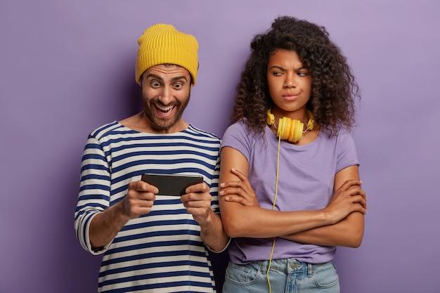 Süchtiger hipster-typ spielt smartphone, ignoriert freundin, afro-frau langweilt sich, hält die arme verschränkt und sieht negativ aus.