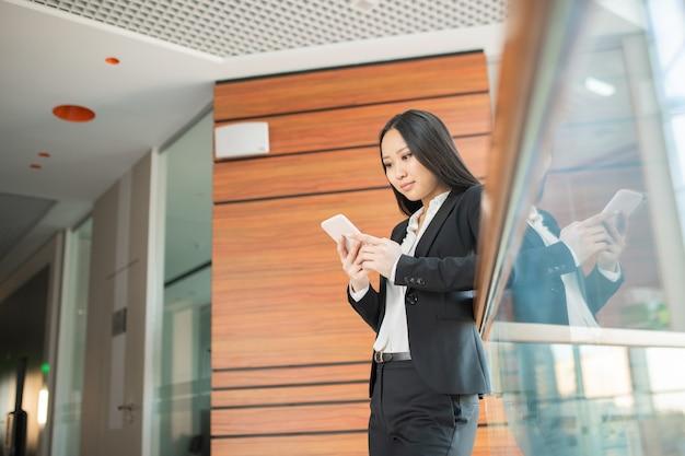Süchtiger junger asiatischer manager in der abendgarderobe, der am geländer steht und soziale medien am telefon überprüft